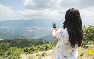 Greece, Central Macedonia, woman taking smartphone picture iの写真素材 [FYI04336879]
