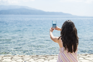 Greece, Sergoulas, woman taking pictures with smartphone atの写真素材 [FYI04336883]