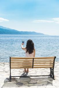 Greece, Sergoulas, woman sitting on bench at the coast takinの写真素材 [FYI04336885]