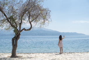 Greece, Sergoulas, woman taking pictures with smartphone atの写真素材 [FYI04336886]