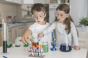 Boy and girl playing science experiments at homeの写真素材 [FYI04336893]