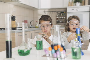 Boy and girl playing science experiments at homeの写真素材 [FYI04336894]