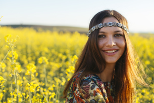 Portrait of smiling young hippie in a rape fieldの写真素材 [FYI04336896]