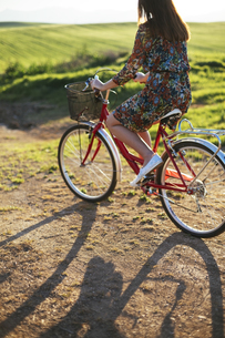 Young woman wearing dress with floral design riding bicycleの写真素材 [FYI04336897]