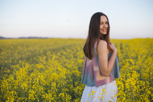 Smiling young woman standing in a rape fieldの写真素材 [FYI04336900]