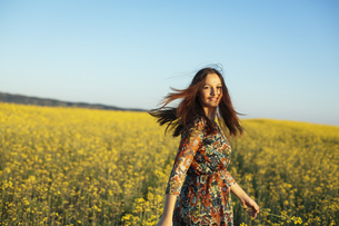 Portrait of smiling young woman standing in a rape fieldの写真素材 [FYI04336901]