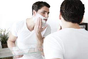 Young man standing in front of mirror, applying shaving foamの写真素材 [FYI04336918]
