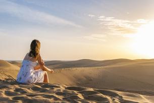 Woman sitting on dune, contemplatingの写真素材 [FYI04336919]