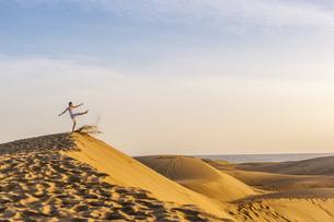 Woman on dune kicking sandの写真素材 [FYI04336920]