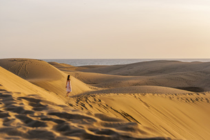 Woman walking over sand dunesの写真素材 [FYI04336921]