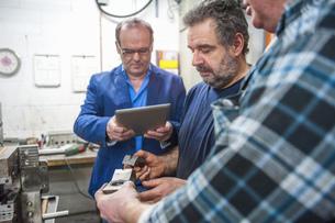Three men with digital tablet examining workpiecesの写真素材 [FYI04336933]