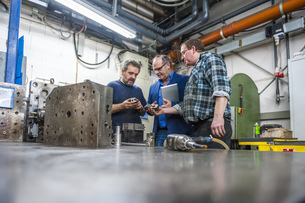 Three men in factory discussing workpiecesの写真素材 [FYI04336934]