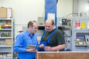 Two men in factory talking in a factoryの写真素材 [FYI04336951]