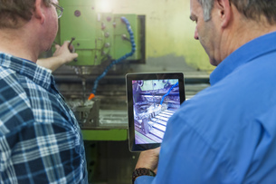 Two men in factory with digital tablet at a machineの写真素材 [FYI04336959]