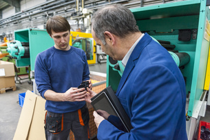 Manager and worker in plastics factory discussing productionの写真素材 [FYI04336994]