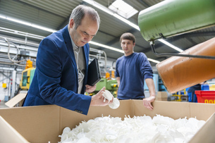 Manager and worker examining products in plastcs factoryの写真素材 [FYI04337002]