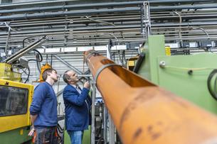 Two people in plastics factory examining machinesの写真素材 [FYI04337003]