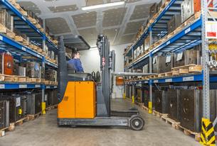 Warehouse worker driving forklift in storage for machine bloの写真素材 [FYI04337012]
