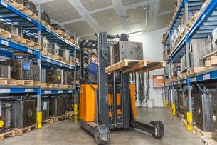 Warehouse worker driving forklift in storage for machine bloの写真素材 [FYI04337013]