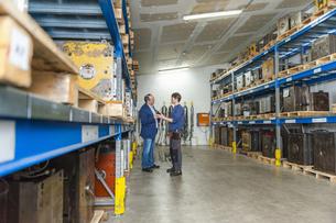 Two men examining machine blocks in storehouseの写真素材 [FYI04337014]