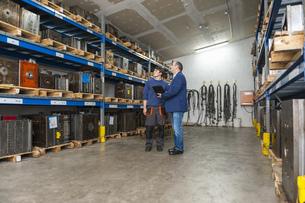 Two men examining machine blocks in storehouseの写真素材 [FYI04337015]