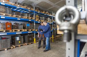 Two men examining machine blocks in storehouseの写真素材 [FYI04337017]