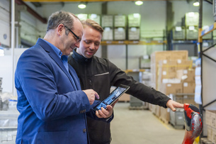 Manager and warehouseman dicussing logistics in storageの写真素材 [FYI04337040]