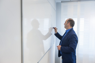 Manager in office writing on white boardの写真素材 [FYI04337042]