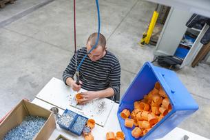 Worker in factory assembling plastic connectorsの写真素材 [FYI04337045]