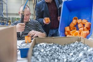 Worker in factory assembling plastic connectorsの写真素材 [FYI04337046]