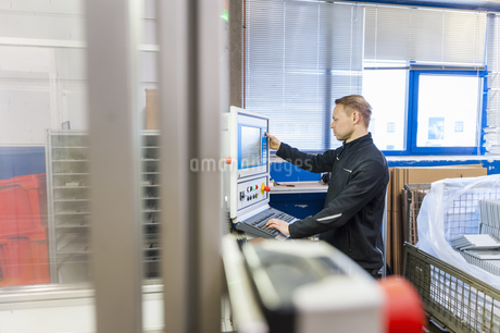 Man working at packaging machine in factoryの写真素材 [FYI04337061]