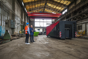 Manager and worker talking at container in factory hallの写真素材 [FYI04337070]