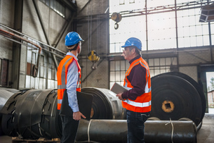 Two men with safety vests in factory hall with rolls of rubbの写真素材 [FYI04337074]