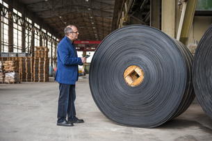 Manager with digital tablet in factory hall with rolls of ruの写真素材 [FYI04337087]