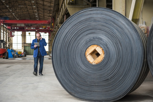 Manager with digital tablet in factory hall with rolls of ruの写真素材 [FYI04337088]