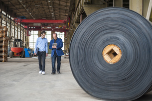 Two men walking in factory hall with rolls of rubberの写真素材 [FYI04337089]
