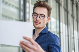 Portrait of young businessman with  digital tablet in frontの写真素材 [FYI04337104]