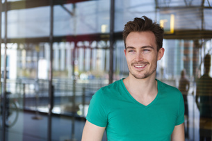 Portrait of smiling young man with stubble standing in frontの写真素材 [FYI04337105]