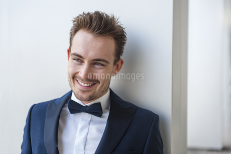 Portrait of smiling young man wearing suit and bow tieの写真素材 [FYI04337107]
