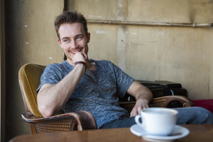 Portrait of happy young man sitting in a coffee shopの写真素材 [FYI04337109]