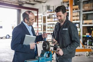 Engineer with digital tablet in workshop, man workingの写真素材 [FYI04337119]