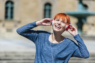 Happy young woman listening to music outdoorsの写真素材 [FYI04337138]