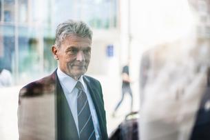 Senior man in suit looking at shop windowの写真素材 [FYI04337154]