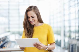 Smiling brunette woman looking at digital tabletの写真素材 [FYI04337159]
