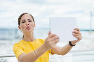 Brunette woman taking a selfie with digital tabletの写真素材 [FYI04337160]