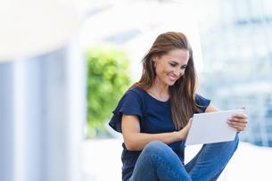 Smiling brunette woman using digital tabletの写真素材 [FYI04337163]