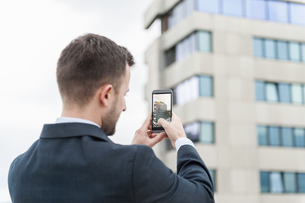 Businessman taking a cell phone picture of an office buildinの写真素材 [FYI04337165]