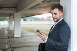 Businessman looking at cell phone in parking garageの写真素材 [FYI04337166]