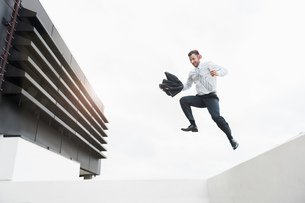 Happy businessman wearing headphones jumping from wallの写真素材 [FYI04337169]