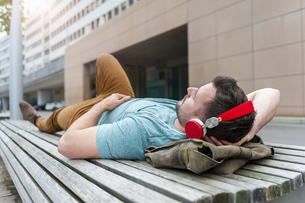 Relaxed young man lying on bench listening to musicの写真素材 [FYI04337172]